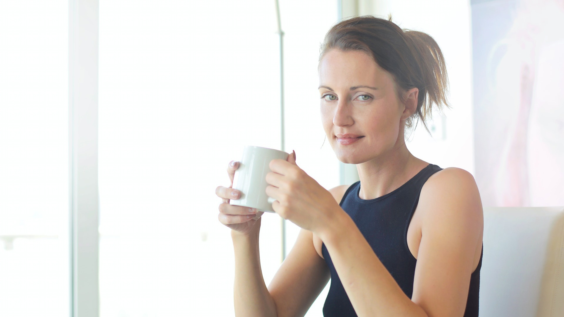 confident woman in black drinking coffee after information sharing with business partners